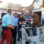 Ministerpräsident Weil, Bürgermeister Dr. Gans und Ortsbrandmeister Wiedemann werden vor dem Ausflug mit der Drehleiter zur eigenen Sicherheit angegurtet
