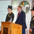 Flankiert von zwei Schornsteinfegern hält Bürgermeister Thomas Gans sein Grußwort.