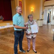 Dr. Gans überreicht die Urkunde für den Ehrenamtspreis an Christa Koch