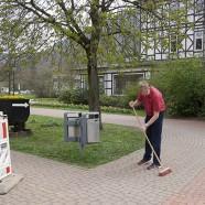 Bürgermeister Dr. Thomas Gans fegt den Bürgersteig und bereitet damit die Fläche für ein Plakat vor.   - Fotos: K.H.Bleß