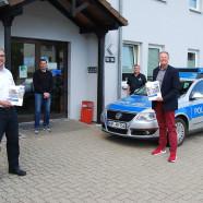 Vor dem Komissariat überreicht EPHK Guido Schwarze den Sicherheitsbericht an Bürgermeister Dr. Gans. (Foto: PK Bad Lauterberg)